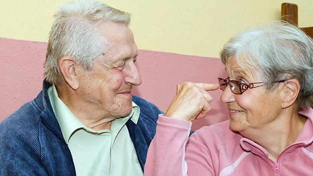 Ein älteres Ehepaar sitzt zu Hause auf dem Sofa.