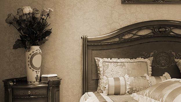 Auf einem Nachttisch neben einem Doppelbett steht ein Strauss Rosen in einer hohen Vase.