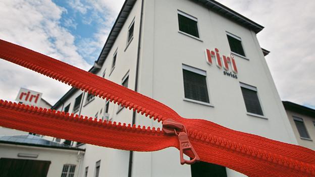 Ein grosser roter Reissverschluss vor einem weissen Gebäude, auf dem riri steht.