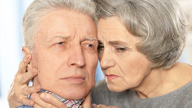 Ein kranker Mann wird von seiner Frau getröstet.