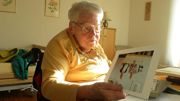 Eine ältere Frau sitzt in einem Rollstuhl an einem Tisch und blättert in einem Fotoalbum.