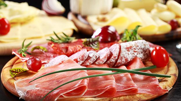 Fleisch und Käse auf Holzplatten.