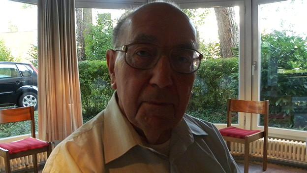 Porträt eines älteren Mannes vor einer grossen Fensterfront.