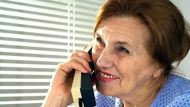 Eine älteres Frau, die am Telefon offensichtlich ein heiteres Gespräch führt.