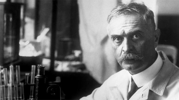 Schwarz-Weiss-Fotografie eines Arztes im weissen Kittel in einem Labor.