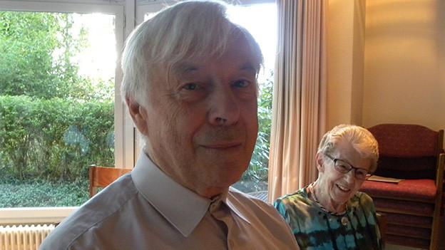 Ein älterer Mann sitzt neben einer Frau am Tisch in einem grossen Aufenthaltsraum.