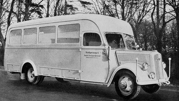 Alte Schwarz-Weiss-Fotografie von einem langen Auto, das einem Bus gleicht.