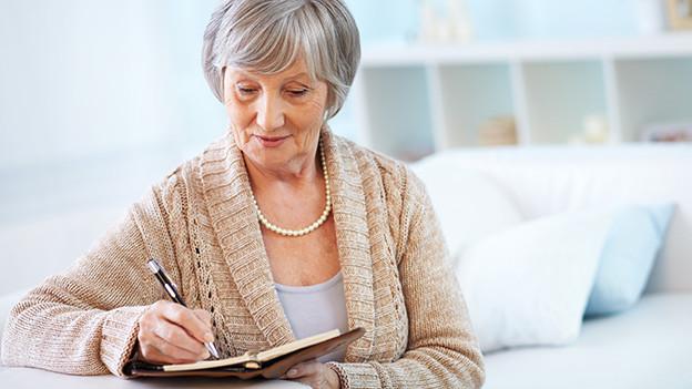 Eine grauhaarige Frau sitzt zufrieden an einem Tisch und studiert ihre Agenda.