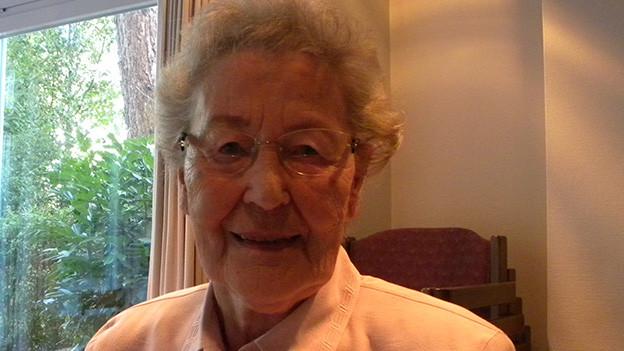 Eine ältere Frau mit Brille sitzt vor einer breiten Fensterfront und lacht in die Kamera.