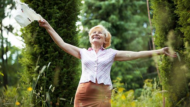 Eine ältere Frau steht mit ausgebreiteten Armen und fröhlich lachend auf einer Wiese.