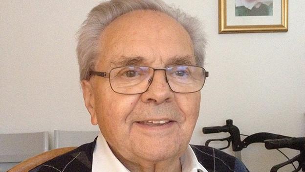 Ein älterer Mann mit grauen Haaren und einem karierten Wollpullover.