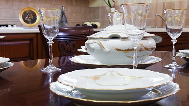 Ein mit Gläsern, Tellern und Besteck gedeckter Tisch.