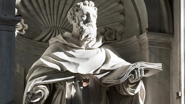 Eine Statue aus Stein mit einem Mann, der ein offenes Buch in der Hand hält.