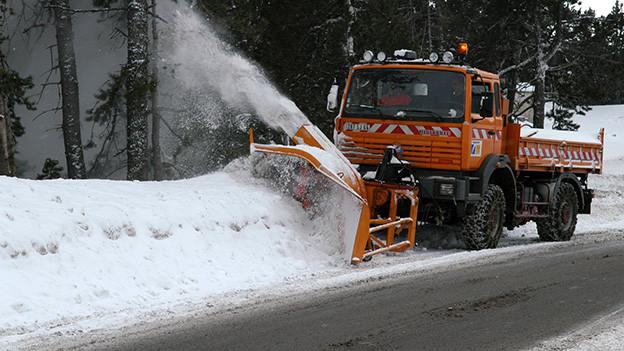 Ein grosser oranger Schneepflug räumt die Strasse frei.