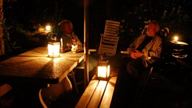 Zwei Männer plaudern bei Kerzenschein.