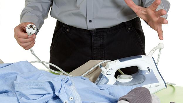 Ein Mann steht mit ringenden Händen vor einem Haufen Wäsche und hält das Kabel eines Bügeleisens in der Hand.