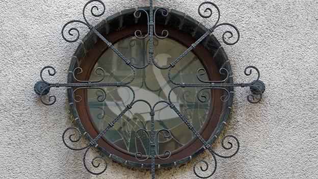 Ein rundes Fenster mit einem kunstvoll verzierten Eisengitter.