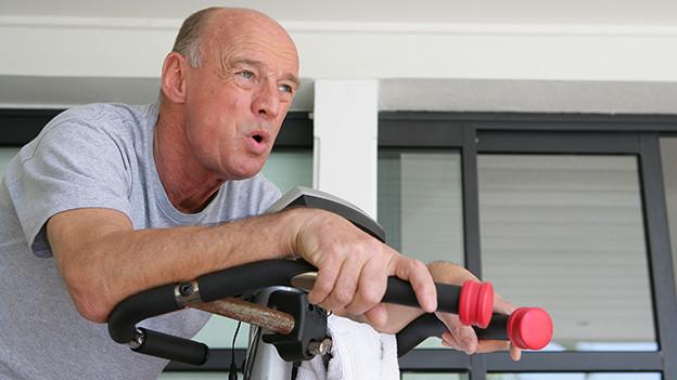 Ein schwitzender Mann an einem Fitnessgerät.