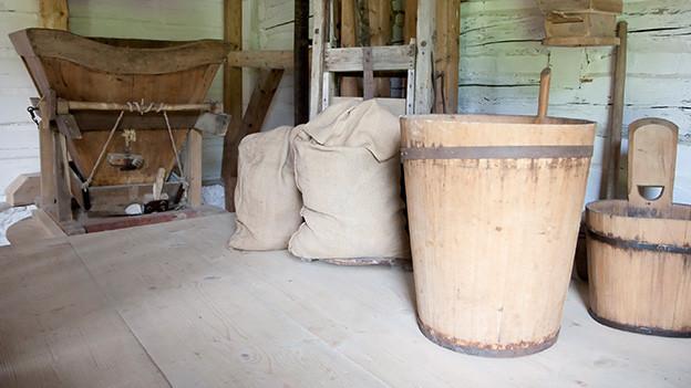 Eine alte Mühle mit Holzeimer und gefüllten Jutesäcken.
