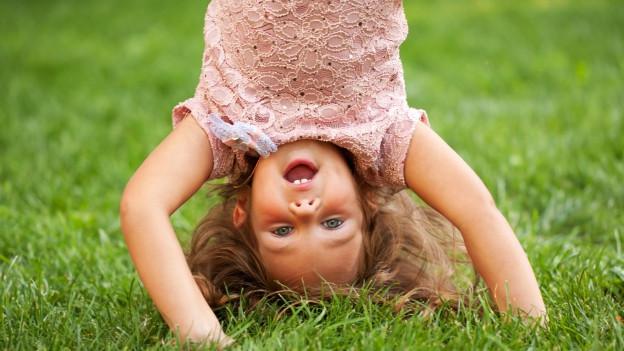 Kleines Mädchen schlägt Purzelbaum.