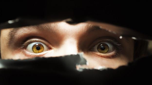 ängstliche Augen schielen durch ein Loch in der Wand.