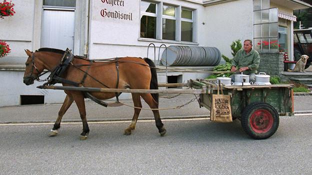 Ein Pferd sitzt einen kleinen Wagen, auf dem ein Mann neben ein paar grossen Milchkannen sitzt.