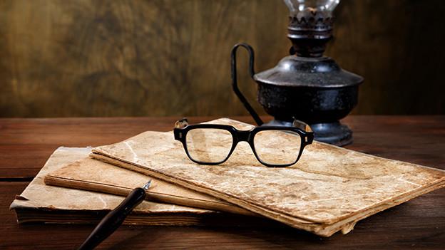 Stillleben mit Pergamentpapier, Brille und antiker Öllampe.