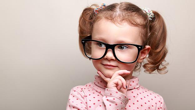 Ein kleines Mädchen trägt eine übergrosse Brille und hält sich nachdenklich die Hand ans Kinn.