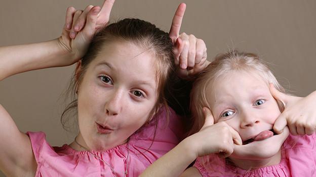 Zwei kleine Mädchen machen Faxen.