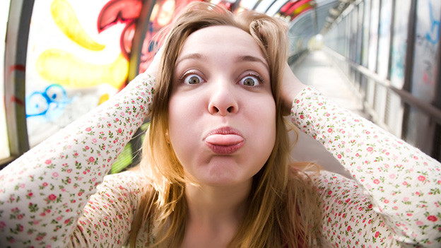 Eine junge Frau greift sich an den Kopf und streckt ihre Zunge heraus.
