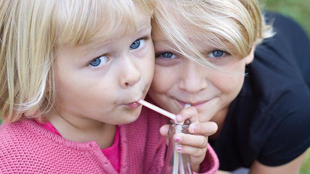 Zwei kleine Mädchen trinken mit einem Strohhalm.