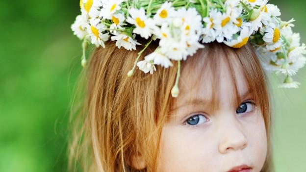 Junges Mädchen mit Blumenkranz auf Kopf.
