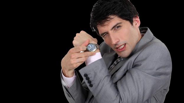 Mann zeigt genervt auf seine Armbanduhr.