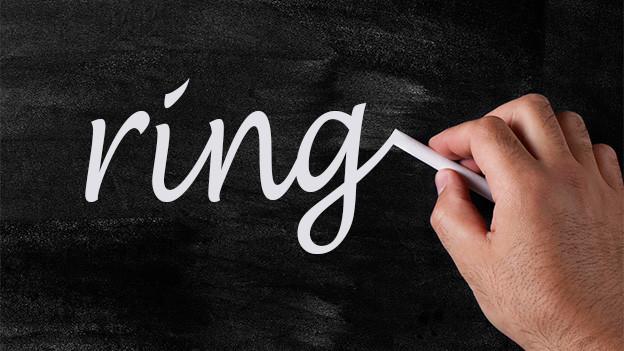 Eine Hand schreibt auf eine Wandtafel das Wort «ring».