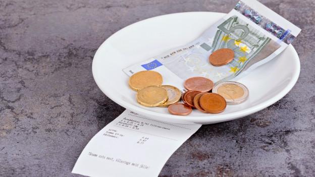 Geld liegt neben Rechnung auf Teller bereit für den Kellner.