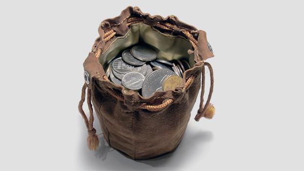 Ein Beutel aus altem Leder, gefüllt mit alten Silbermünzen.
