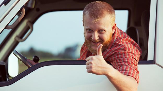 Ein Lastwagenchauffeur blickt lachend aus dem Seitenfenster und hält einen Daumen hoch.