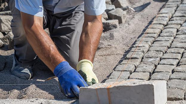 Ein Handwerker kniet am Boden und verlegt Pflastersteine.
