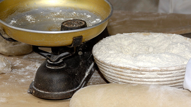Stilleben mit Waage, Mehl und Brot.