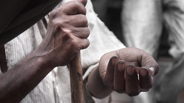 Ein Bettler mit einem Stock hält eine offene Hand hin.