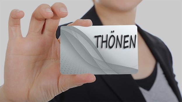 Konturen einer Frau, die eine Visitenkarte mit dem Namen Thönen zeigt.