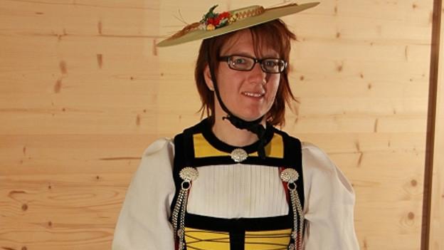 Eine Trachtenfrau mit Strohhut.