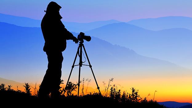 Ein Mann steht bei Sonnenuntergang vor einer Kamera, die auf ein Stativ montiert ist.