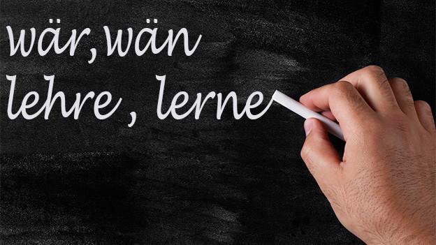 Mit Kreide geschriebene Wörter auf einer Wandtafel.