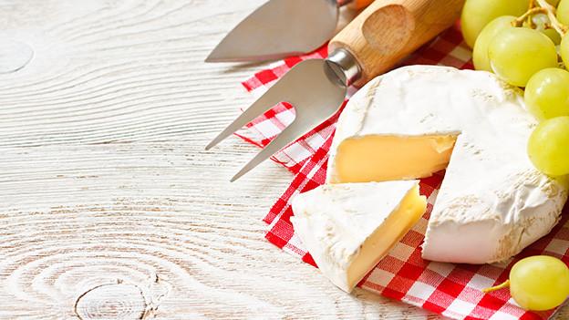 Käseplatte mit Camembert und Trauben.