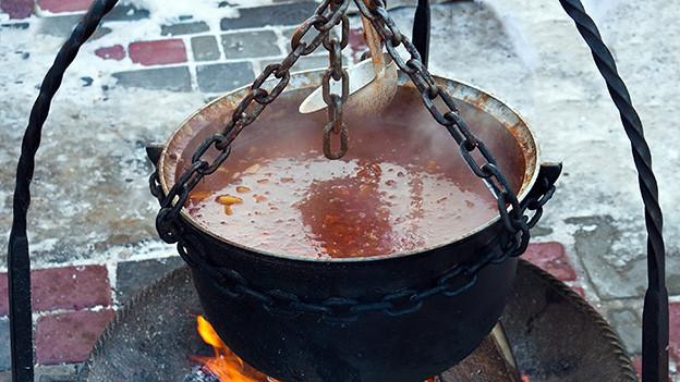 Eine Suppe kocht in einem Kupferkessel über einem offenen Feuer.