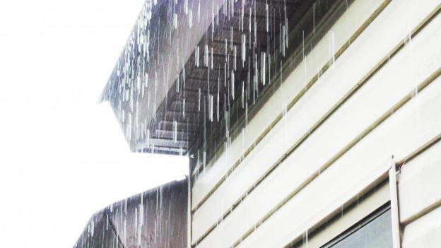 Regen prasselt auf ein Hausdach.