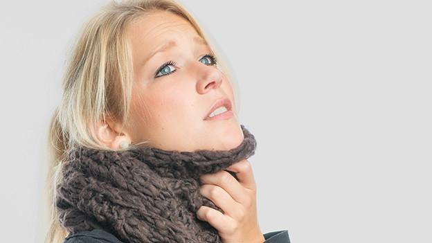 Eine Frau trägt einen dicken Wollschal und hält sich eine Hand an den Hals.