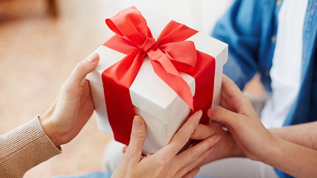 Hände, die ein Geschenk halten.