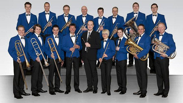 Gruppenbild mit Blasmusikantinnen und Blasmusikanten in blau-schwarzen Uniformen.